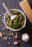Igreen pesto in mortar and ingredients closeup.vertical top view Royalty Free Stock Photography