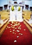 Igreja à cerimônia de casamento, pétalas da decoração em um tapete vermelho Foto de Stock Royalty Free