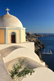 Igreja amarela de Santorini acima do mar Fotos de Stock Royalty Free