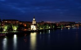 A igreja bonita com iluminação na noite, luzes refletiu na água Vista da terraplenagem de Dnipropetrovsk, Ucrânia Imagens de Stock Royalty Free