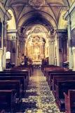 Igreja Cat?lica hist?rica: Bancos de madeira em seguido e crucifixo da largura do altar imagens de stock royalty free