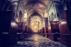 Igreja Cat?lica hist?rica: Bancos de madeira em seguido e crucifixo da largura do altar fotos de stock