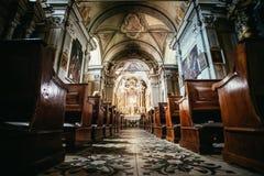 Igreja Cat?lica hist?rica: Bancos de madeira em seguido e crucifixo da largura do altar imagens de stock