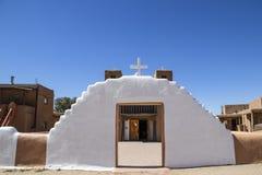 A igreja da missão do povoado indígeno da lama de Adobe com porta ao pátio da plaza pintou a porta de entrada do branco e da miss imagem de stock royalty free