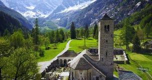 Igreja da montanha na bandeja dianteira aérea dos cumes italianos com a montanha no fundo vídeos de arquivo
