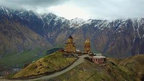 Igreja da peregrinação de Zminda Sameba, Cáucaso alto, nas nuvens, Stepanzminda, Geórgia video estoque