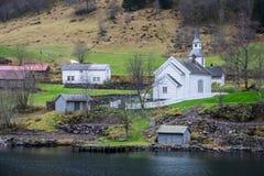 Igreja de madeira branca pequena em uma costa do fiorde fotos de stock