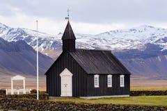 Igreja de madeira preta em Islândia na perspectiva das montanhas Igreja de Budir imagem de stock