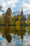 Igreja de madeira velha refletida na lagoa Árvore espelhada no wate Foto de Stock Royalty Free