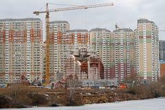 Igreja de Nikolskaya sob a construção no fundo de construções residenciais em Moscou Fotografia de Stock