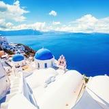 Igreja de Santorini e casas brancas contra o céu azul com nuvens Vila bonita de Oia, marco de Grécia fotografia de stock