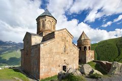 Igreja de trindade de Gergeti, Tsminda Sameba no céu azul com fundo das nuvens em Geórgia imagens de stock royalty free