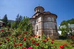 Igreja do monastério de Cozia com flores vermelhas em um dia de verão ensolarado imagens de stock royalty free