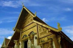 Igreja dourada com arquitetura velha do fundo do céu azul no templo de Wat Phra Singh em Chiang Rai fotos de stock royalty free