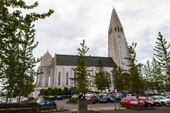 Igreja em Reykjavik, em árvores e na opinião lateral dos carros imagens de stock royalty free