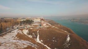 A igreja em um penhasco sobre o rio Siberian da montanha video estoque