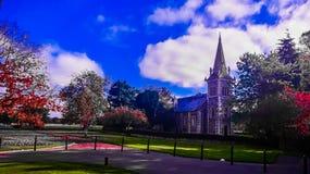 Igreja entre o céu azul e as folhas vermelhas fotografia de stock