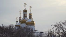 Igreja grande, bonita com a neve que encontra-se em abóbadas douradas no fundo claro, cinzento do céu estoque Paisagem do inverno vídeos de arquivo