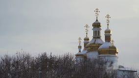 Igreja grande, bonita com a neve que encontra-se em abóbadas douradas no fundo claro, cinzento do céu estoque Paisagem do inverno filme