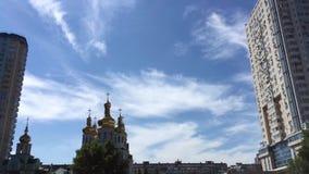 A igreja na cidade e o céu azul com nuvens decorrem a tempo vídeos de arquivo