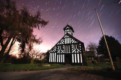Igreja na noite com fugas da estrela Fotografia de Stock Royalty Free
