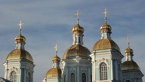 Igreja ortodoxa azul com abóbadas e cruzes douradas contra um céu azul video estoque