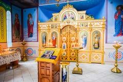 Igreja ortodoxa do interior Velas ardentes da cera na frente dos ícones e dos fresco Religião cristã Imagens de Stock Royalty Free