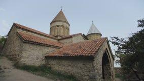 Igreja ortodoxa velha da pedra e tijolo com telhado telhado e torres altas, montanhas de Geórgia video estoque