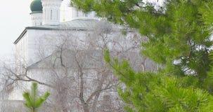 Igreja ortodoxa velha do russo no Kremlin de Astracã, olhar de Rússia através dos ramos de árvore sempre-verdes no inverno video estoque