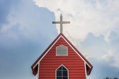 Igreja transversal com construção vermelha e o céu azul | Lugar e símbolo cristãos da religião Foto de Stock