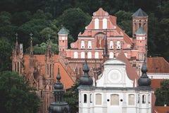 Igrejas históricas múltiplas cercadas por árvores verdes em Vilnius, Lituânia Fotografia de Stock Royalty Free