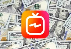 IGTV icon printed on paper, cut and placed on money background stock photo