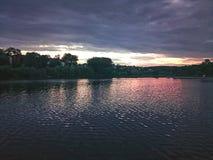 Igualación de puesta del sol roja y púrpura en el lago fotografía de archivo