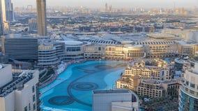 Igualando las fuentes del baile de la visión aérea en el centro de la ciudad y en un timelapse del lago artificial en Dubai, UAE almacen de metraje de vídeo