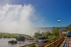 IGUAZU, ARGENTINA - MAY 14, 2016: argentinas flag waving at the top of the waterfalls, mist provocated because of the Royalty Free Stock Photography