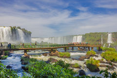 IGUAZU, BRAZIL - MAY 14, 2016: little bridge over the river close to the bottom of the falls, lot of people taking Royalty Free Stock Photo