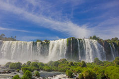 IGUAZU, BRAZIL - MAY 14, 2016: nice view from the bottom of the waterfalls, some rocks covered by grass in front of the. Waterfall and blue sky as background Royalty Free Stock Photo