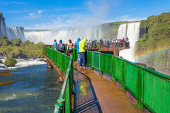 The Iguazu Falls. Tourists near the Iguazu Falls, waterfalls of the Iguazu River on the border of the Argentina and the Brazil. It's one of the New 7 Wonders of Stock Image