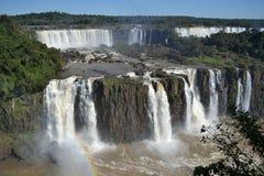Iguazu-Wasserfallregenbogen auf sonnigem, blauem Himmel Lizenzfreie Stockbilder