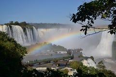 Iguazu-Wasserfallregenbogen auf sonnigem, blauem Himmel und Brücke Lizenzfreie Stockfotografie