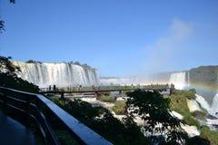 Iguazu-Wasserfallregenbogen auf sonnigem, blauem Himmel und Brücke Stockfotos