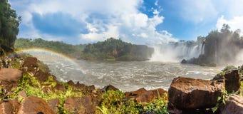 Iguazy下跌有小瀑布蒸和彩虹的瀑布的全景 免版税库存图片