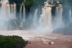Iguazzu Falls, South America. A boat full of tourists enjoy a close-up view of the falls , bordering Argentina and Brazil Royalty Free Stock Images