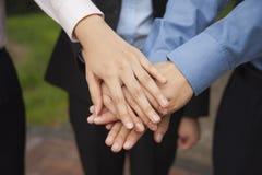 Ihre Hand als Zeichen der Teamfunktion zusammenfügende und zujubelnde Geschäftsleute, Nahaufnahme Lizenzfreie Stockfotos