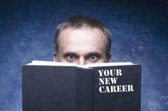IHRE NEUE KARRIERE geschrieben auf die Abdeckung des Buches, reifer Mann fokussierend und durch Buch, überraschter offener Buh de lizenzfreie stockfotos