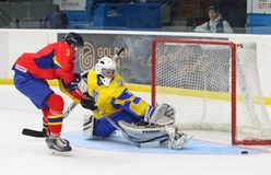 IIHF 2018 Ice Hockey U18 World Championship Div 1B. KYIV, UKRAINE - APRIL 20, 2018: Player Huba SILLO of Romania L attacks goalkeeper Vladyslav HURKO of Ukraine royalty free stock image