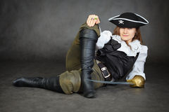 Iimpudent woman pirate lies with sabre on black Royalty Free Stock Photography