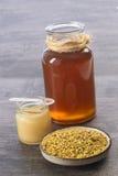 Iin de oro del polen de la abeja a la taza con la jalea real y la miel en vidrio del tarro Fotos de archivo