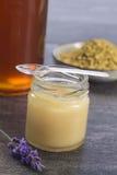Iin de oro del polen de la abeja a la taza con la jalea real y la miel en vidrio del tarro Fotografía de archivo libre de regalías