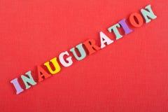 Iinauguration Engelska uttrycker på röd bakgrund som komponeras från träbokstäver för färgrikt abc-alfabetkvarter, kopieringsutry Arkivbild